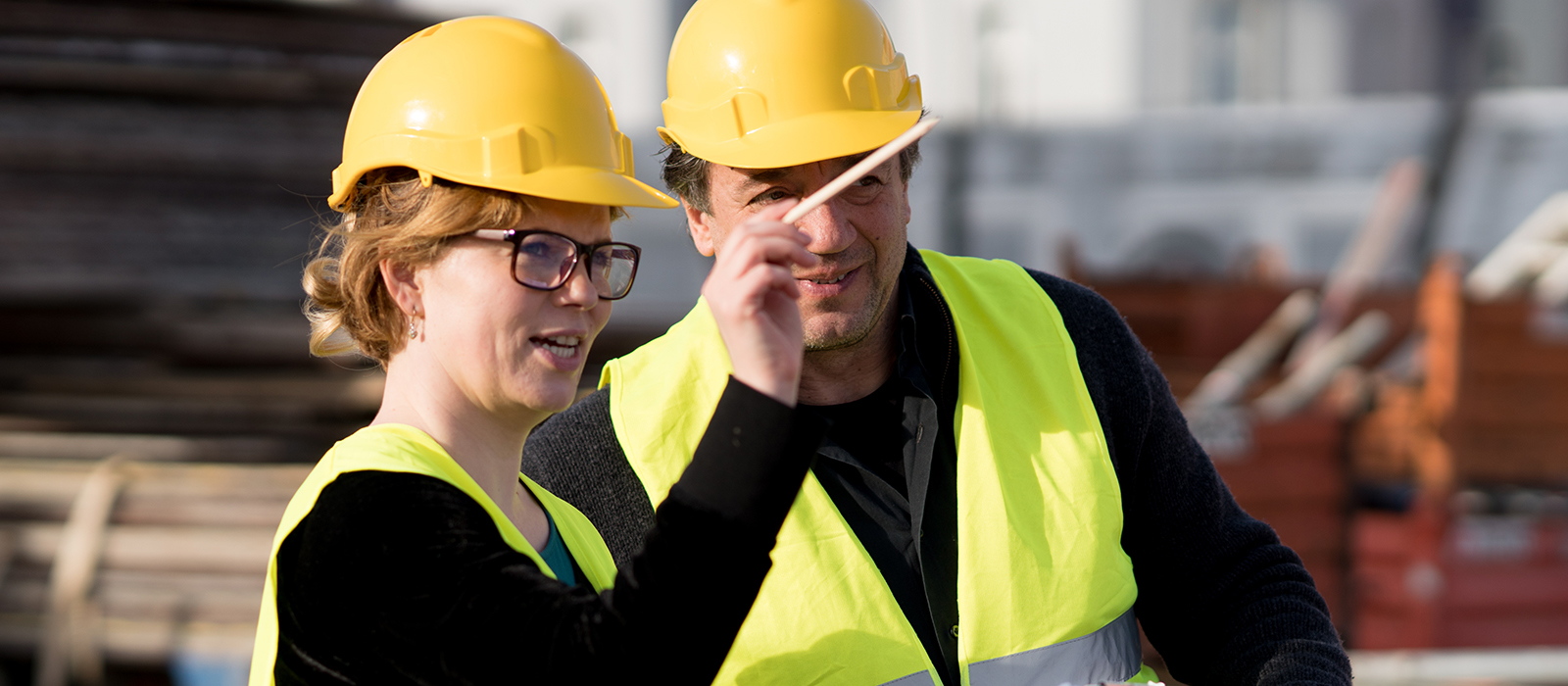 Two persons with high-visibility vest and yellow construction worker helmet are talking