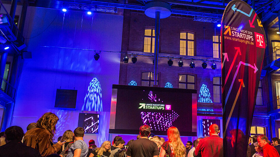 In the background you can see a blue illuminated house wall. A screen is placed in front of the wall. Participants are looking at it.