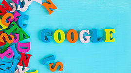 Google - word composed of small colored letters on blue background