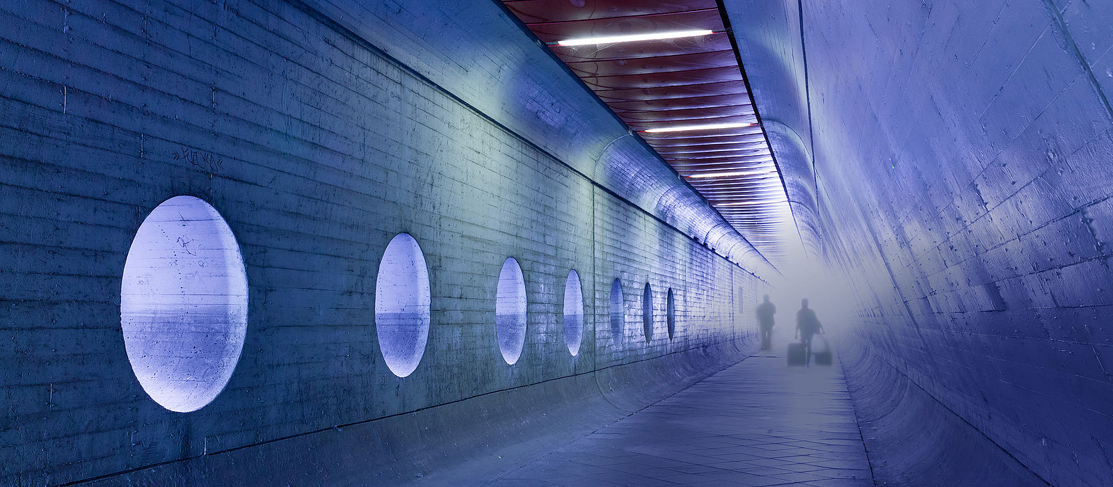 A woman and a man walk through a pedestrian tunnel towards the illuminated exit, pulling trolleys.